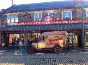 An old co-op shop with a Newcastle Breweries van parked outside.
