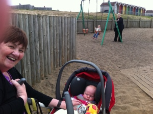 Picture of my mum, daughter, aunt & niece playing at South Beach Park with colourful beach huts in the background.